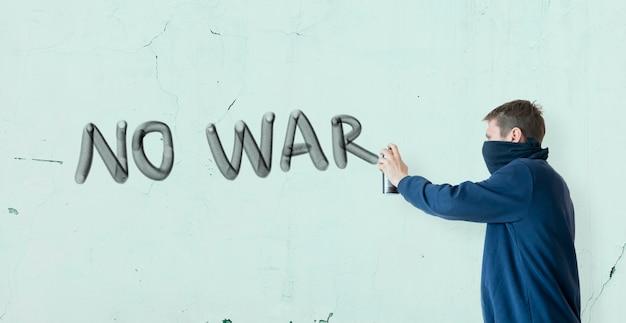 Ein mann, der mit sprühfarbe schreibt, kann die kriegserklärung an der wand stoppen, graffiti-symbolkonzept Premium Fotos