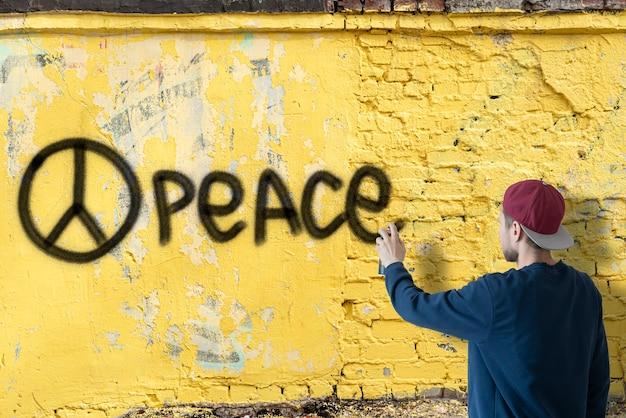 Ein mann, der mit sprühfarbe schreibt, kann die kriegserklärung an der wand stoppen, graffiti-symbolkonzept