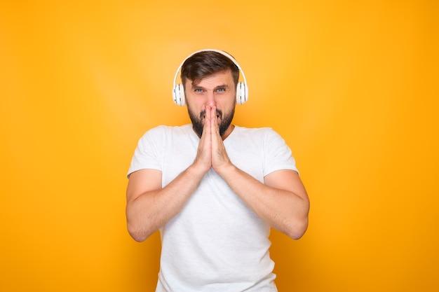Ein mann, der mit weißen kopfhörern musik hörte, verschränkte die handflächen vor dem gesicht.