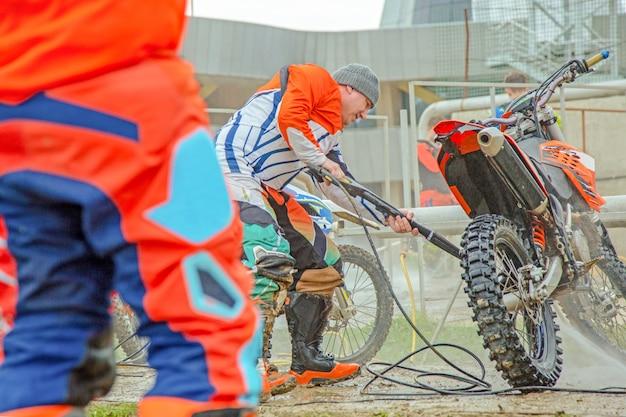 Ein mann, der motorrad - motorrad-detaillierungskonzept reinigt. selektiver fokus.