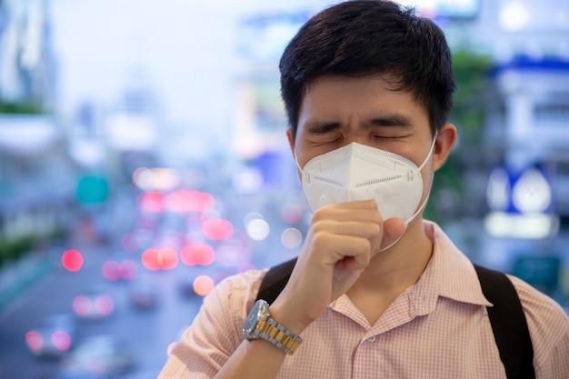 Ein mann, der mundmaske gegen luft smogverschmutzung mit pm 2.5 in bangkok stadt, thailand trägt.