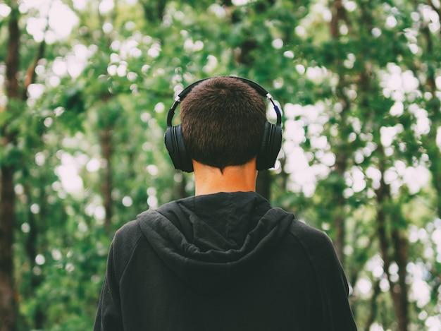 Ein mann, der musik in den kopfhörern obenliegend geht in den park hört