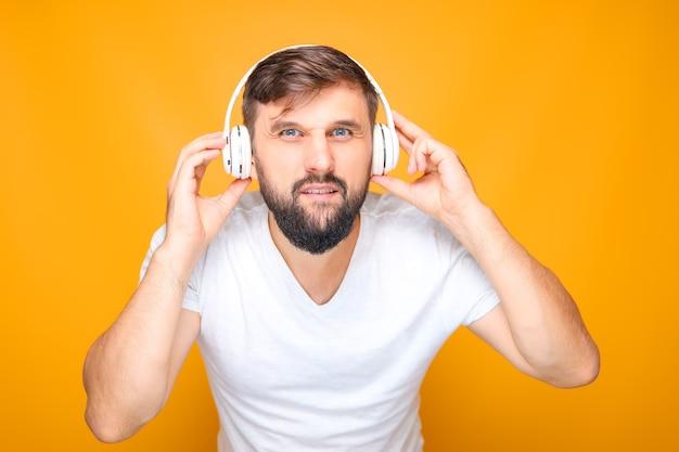 Ein mann, der musikkopfhörer fest an seine ohren drückt und in die kamera schaut.