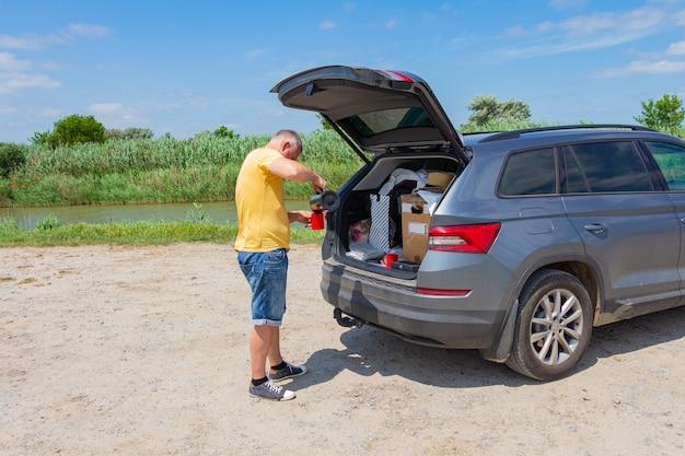 Ein mann, der neben einem auto steht.