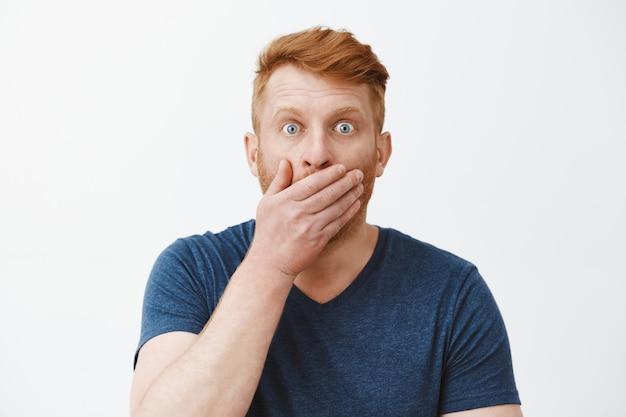 Ein mann, der neue gerüchte schockiert und erstaunt hört, den geöffneten mund mit der handfläche bedeckt, während er nach luft schnappt, mit aufgesprungenen augen starrt, kann nicht glauben, dass etwas schockierendes passiert ist, und klatsch über die graue wand hört