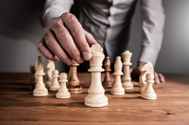 Ein mann, der schach an einer dunklen wand spielt