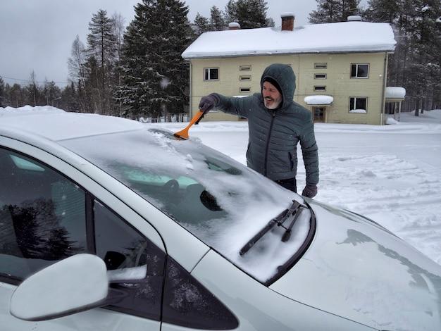 Ein mann, der schnee von der autowindschutzscheibe mit bürste säubert