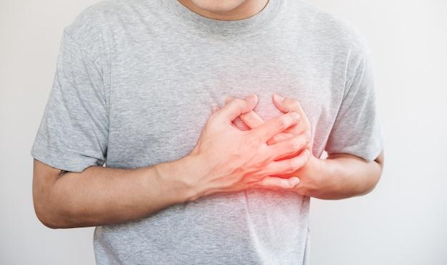 Ein mann, der sein herz, mit rotem höhepunkt des herzinfarkts und anderes herzkrankheitskonzept berührt