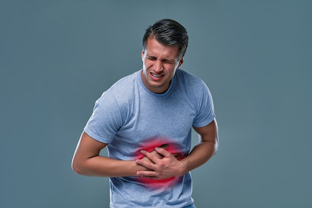 Ein mann, der seinen bauch berührt, auf grauem hintergrund mit kopienraum. magenschmerzen und andere magenerkrankungen konzept.