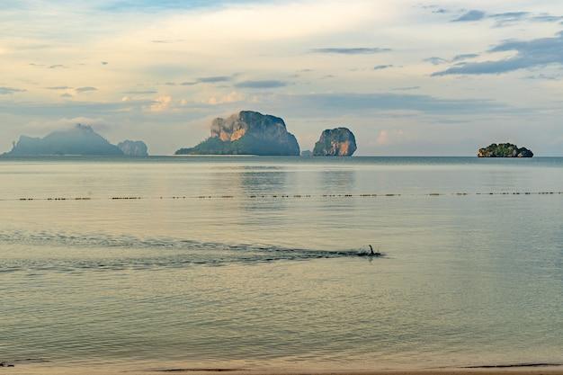 Ein mann, der seinen morgen im meer am pranang cave beach, railay, krabi, thailand schwimmen lässt