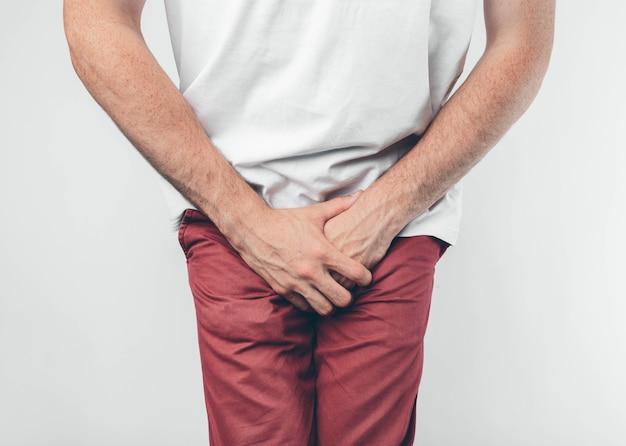Ein mann, der seinen penis mit auf dem weißen hintergrund hält. möchte auf die toilette gehen.