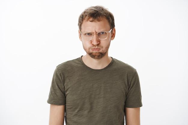 Ein mann, der sich wütend auf freunde fühlt, die den atem anhalten und vor beleidigung und wut schmollen und die stirn runzeln und schwören, sagt kein wort, es sei denn, es tut ihnen leid, kindisch und unzufrieden über der grauen wand in einem dunkelgrünen t-shirt zu stehen