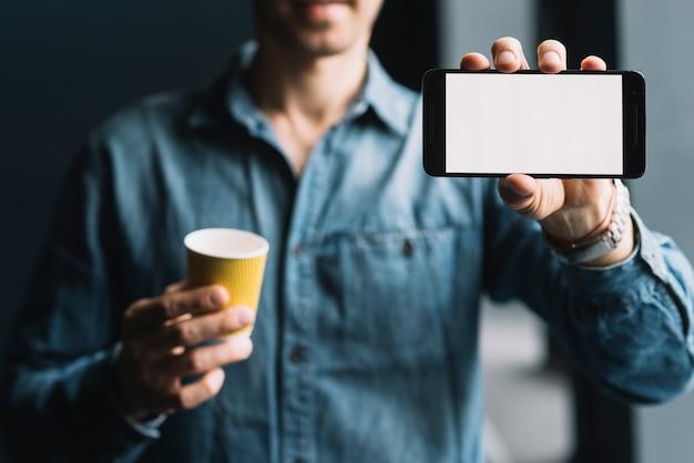 Ein mann, der smartphone mit weißem leerem bildschirm zeigt