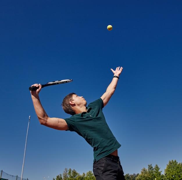 Ein mann, der tennis auf dem platz an einem schönen sonnigen tag spielt