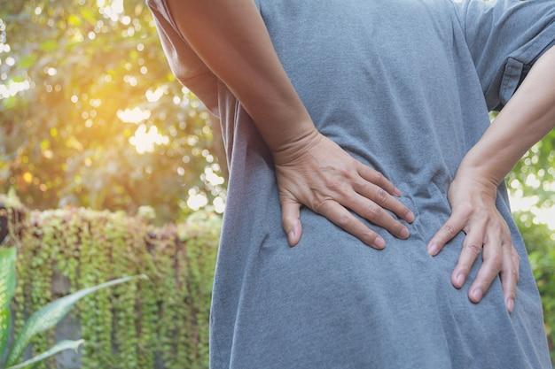 Ein mann, der unter rückenschmerzen-, rückenmarksverletzungs- und muskelproblemproblem am im freien leidet.
