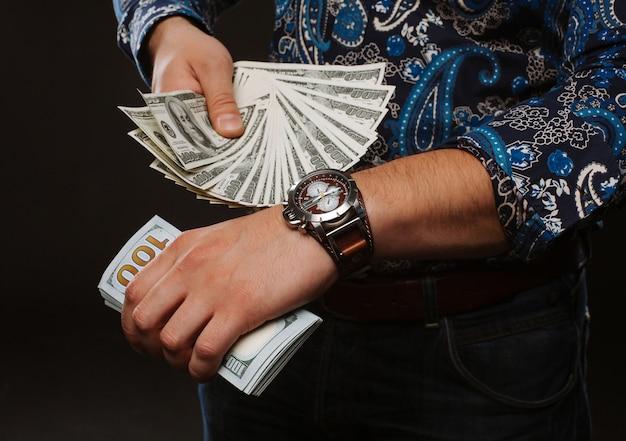 Ein mann, der viel geld in der hand hält und pünktlich auftaucht.