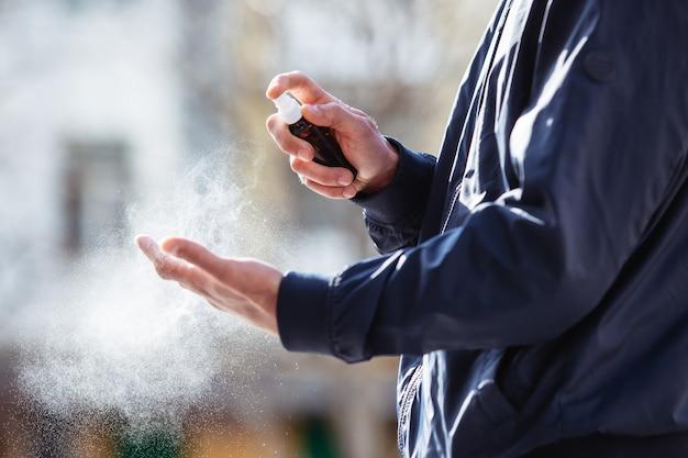 Ein mann desinfiziert seine hände mit einem desinfektionsspray mit alkohol. während einer coronavirus-pandemie. hände schließen.