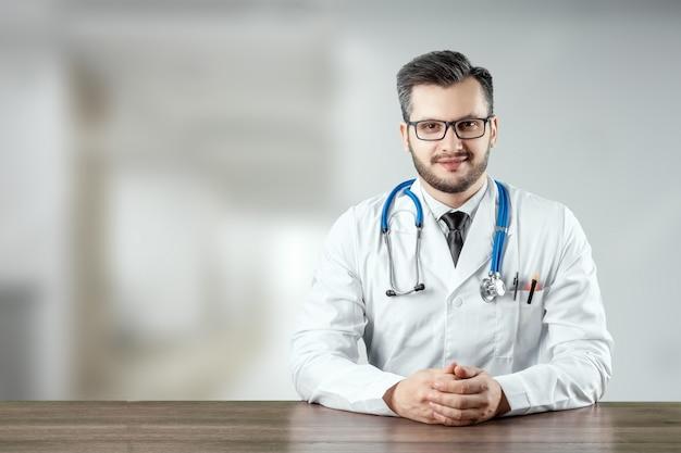 Ein mann, ein arzt in einem weißen kittel mit einem stethoskop