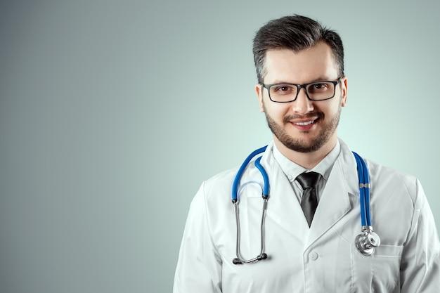 Ein mann, ein arzt in einem weißen kittel mit einem stethoskop.