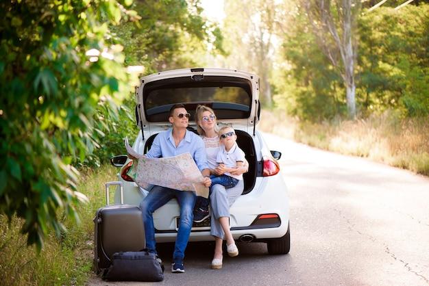 Ein mann, eine frau und ein kind von vier jahren im wald neben dem auto sind bereit zu reisen und einen ort auf der karte auszuwählen, an den sie gehen möchten.