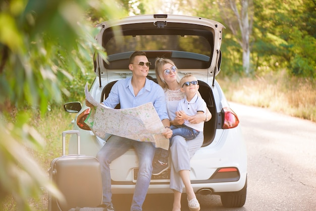 Ein mann, eine frau und ein kind von vier jahren im wald neben dem auto sind bereit zu reisen und wählen einen ort auf der karte, wohin sie gehen sollen.