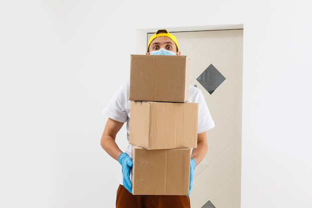 Ein mann, eine medizinische maske und blaue gummihandschuhe mit einer schachtel, ein paket in den händen. lebensmittellieferung während der quarantäne der coronavirus-pandemie. lieferung nach hause, online-bestellung. online einkaufen .