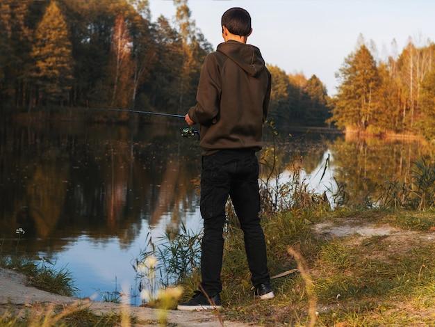 Ein mann fängt im herbst auf dem see fische an einer spinnrute