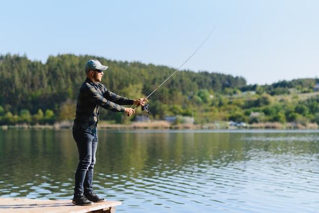 Ein mann fängt im sommer einen fisch beim spinnfischen
