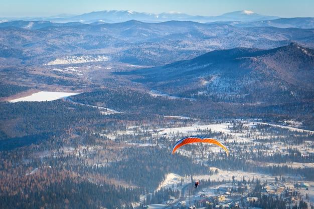 Ein mann fliegt mit einem orangefarbenen fallschirm
