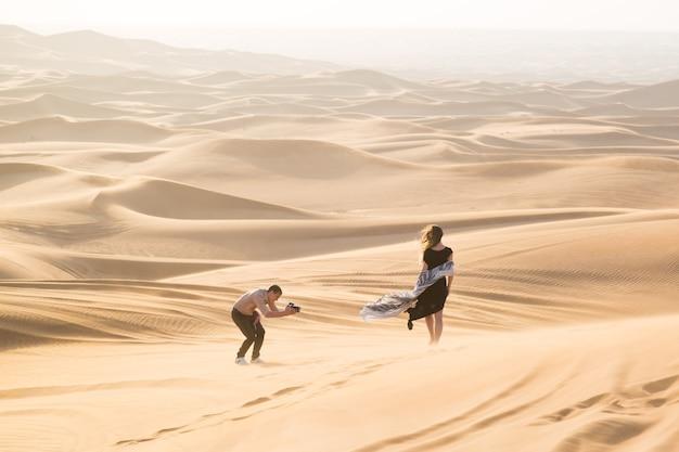 Ein mann fotografiert eine junge frau im sand der wüste bei einem werbeshooting für eine zeitschrift