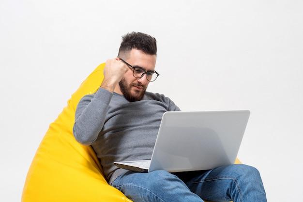 Ein mann freut sich bei der arbeit am laptop
