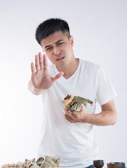 Ein mann fühlt sich krank, nachdem er zu viel zongzi gegessen hat und lehnt es ab, mehr zu essen.