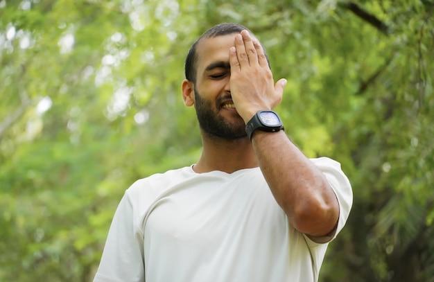 Ein mann fühlt sich schüchtern und glücklich bedeckt sein gesicht