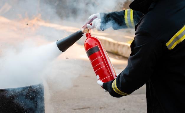 Ein mann führt übungen mit einem feuerlöscher durch. feuerlöschkonzept. brandnotfall