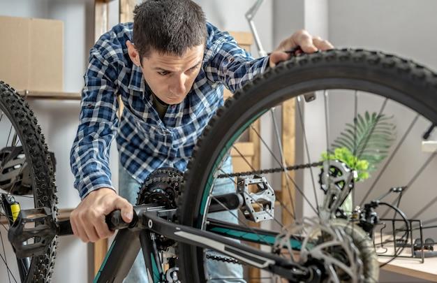 Ein mann führt wartungsarbeiten an seinem mountainbike durch. konzept zur befestigung und vorbereitung des fahrrads für die neue saison