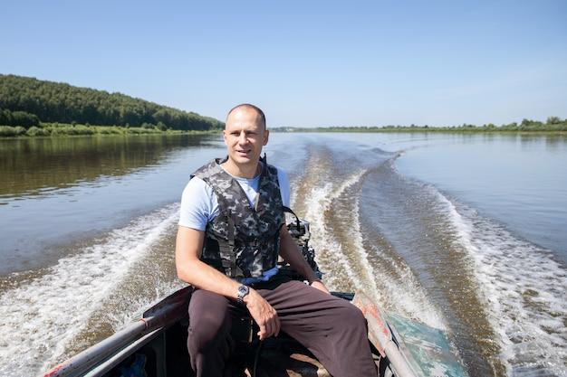 Ein mann geht auf einem motorboot zum fischen des kontrollflusses
