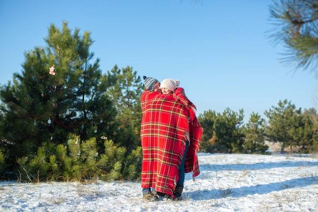 Ein mann geht im winter im wald spazieren und wickelt seine freundin in ein warmes rotes kariertes plaid, damit sie sich wärmt