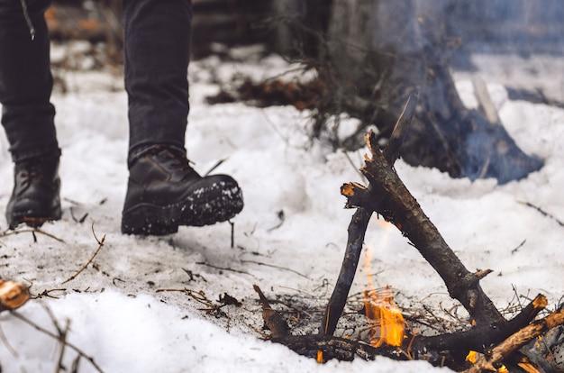Ein mann geht im winter zu einem brennenden lagerfeuer.