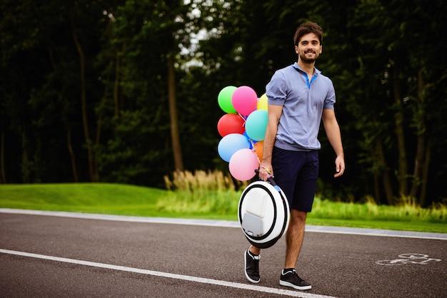 Ein mann geht mit einem monokel in der hand den parkweg entlang