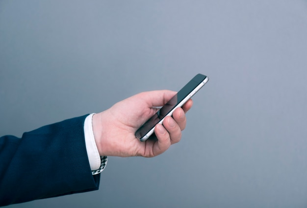 Ein mann geschäftsmann gekleidet im anzug, der smartphone vor grauem hintergrund hält. geschäftskonzept bild.