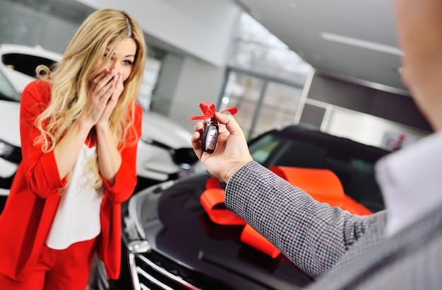 Ein mann gibt einer frau die schlüssel für ein neues auto auf der oberfläche eines schwarzen autos mit einem roten geschenkbogen und einem autohaus