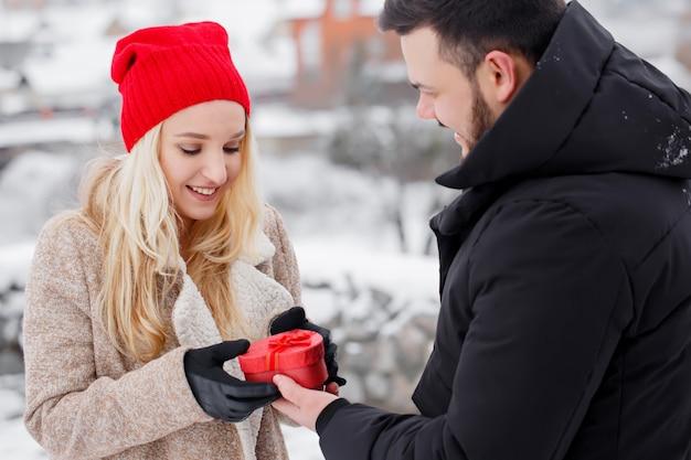 Ein mann gibt seiner freundin eine herzförmige schachtel, ein konzept für den valentinstag