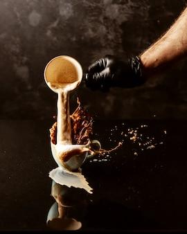Ein mann gießt eine tasse kaffee in eine andere volle tasse und kaffee läuft von den rändern
