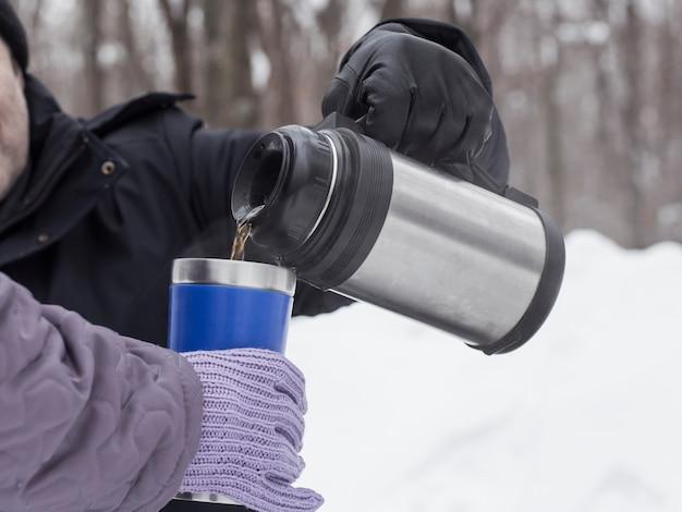 Ein mann gießt einer frau tee aus einer thermoskanne in einer thermoskanne zum trinken und aufwärmen.