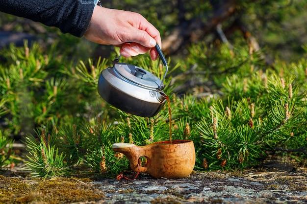 Ein mann gießt köstlichen kaffee aus einem wasserkocher in eine holztasse.