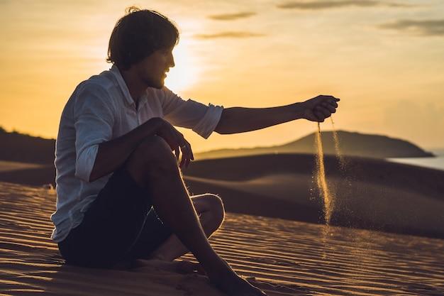 Ein mann gießt sand in die wüste. sand durch die finger des konzepts.