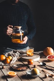 Ein mann gießt zitrus-tee auf einen holztisch. gesundes getränk im vintage-stil. vegane öko-produkte.