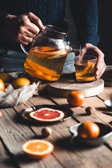 Ein mann gießt zitrus-tee auf einen holztisch. gesundes getränk im vintage-stil.