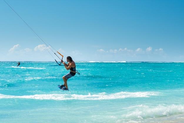 Ein mann gleitschirmfliegen am strand von le morne, mauritius, indischer ozean auf der insel mauritius.