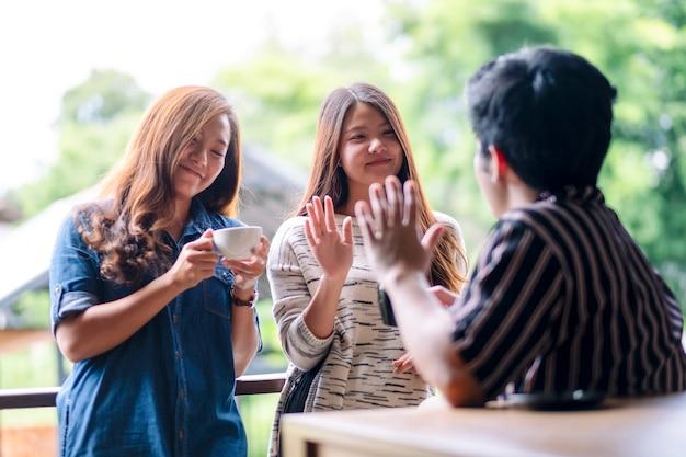 Ein mann grüßt und grüßt seine freundinnen, während er mit kopfhörern musik hört und kaffee trinkt
